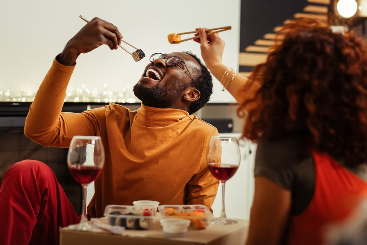 Couple having fun while eating sushi at home after fast delivery